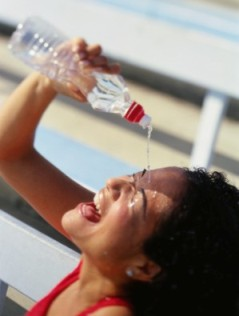 woman pouring water on her face