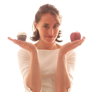 woman holding apple and cupcake